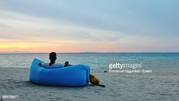 Rear View Of Man Sitting On Inflatable Chair On Beach