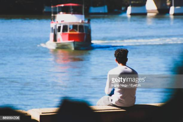 Rear View Of Man Sitting On Jetty By Sea