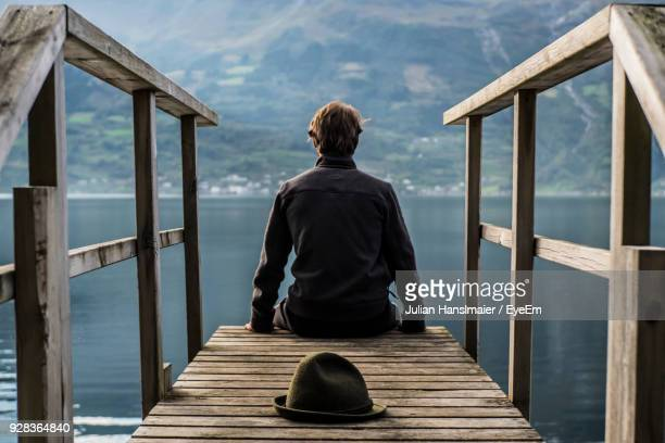 Rear View Of Man Sitting On Jetty