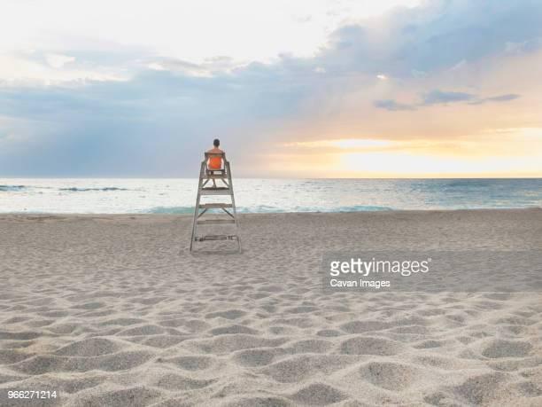 rear view of man sitting on lifeguard hut at beach against cloudy sky during sunset - strandwächterhaus stock-fotos und bilder