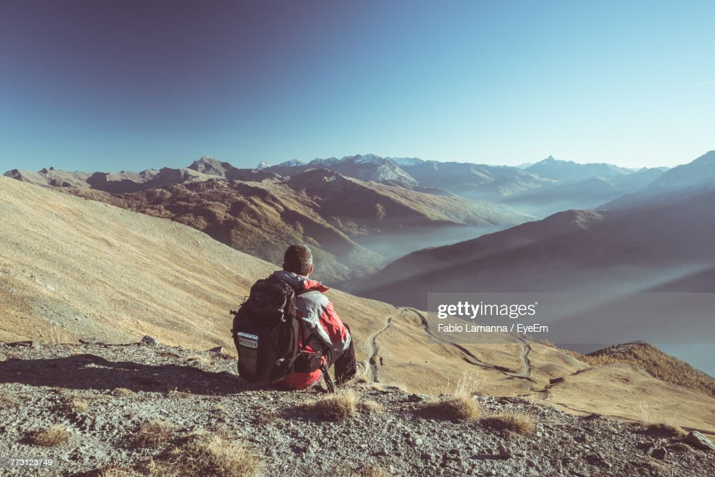 Rear View Of Man Sitting On Mountain Against Clear Blue Sky : Photo