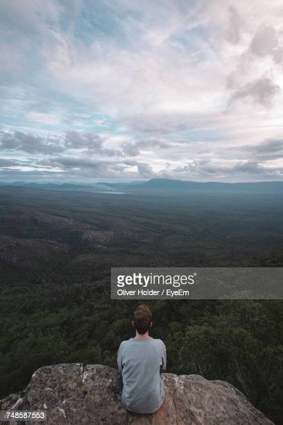 Rear View Of Man Sitting On Mountain And Looking At View Against Cloudy Sky