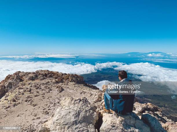 rear view of man sitting on mountain peak against blue sky - bortes stock pictures, royalty-free photos & images