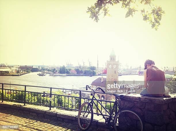 Rear View Of Man Sitting On Railing Against Hamburg Harbor