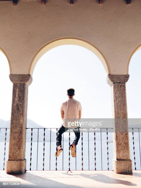 rear view of man sitting on railing against sky - ascona stock photos and pictures