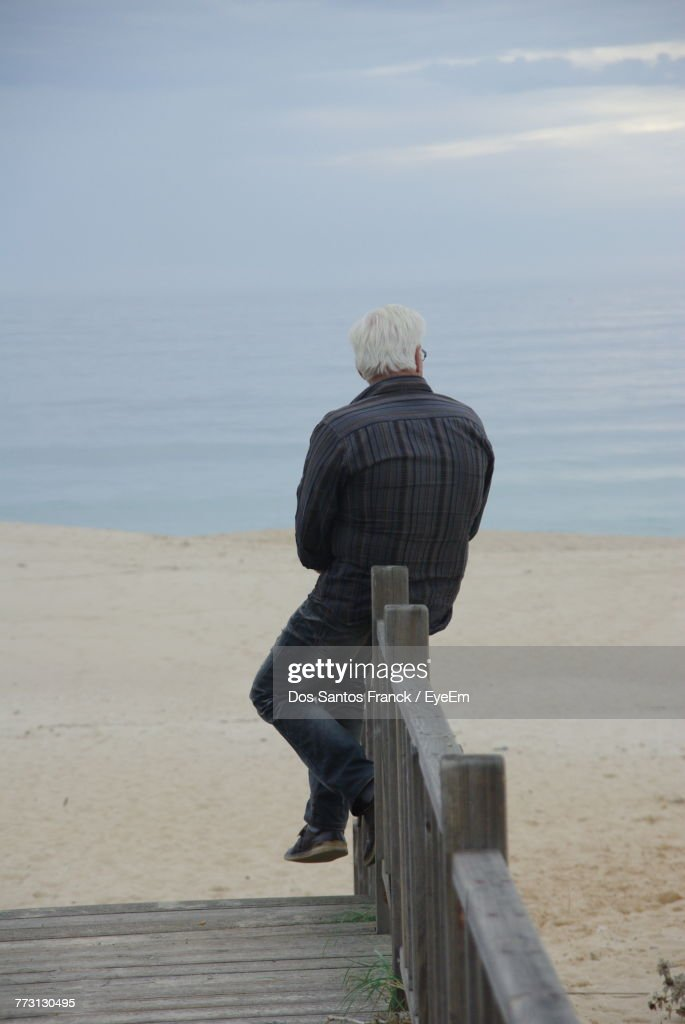 Rear View Of Man Sitting On Railing At Beach Against Sky : Stock Photo