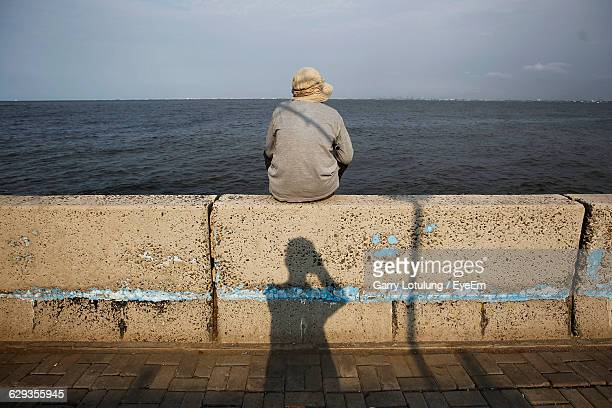 Rear View Of Man Sitting On Retaining Wall With Shadow Of Person At Sea Shore