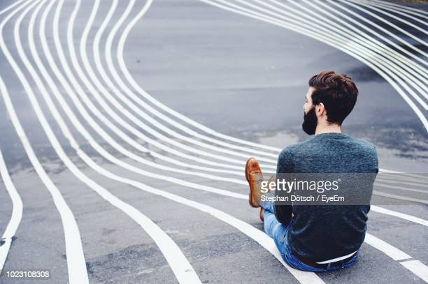 rear view of man sitting on road marking - assis photos et images de collection