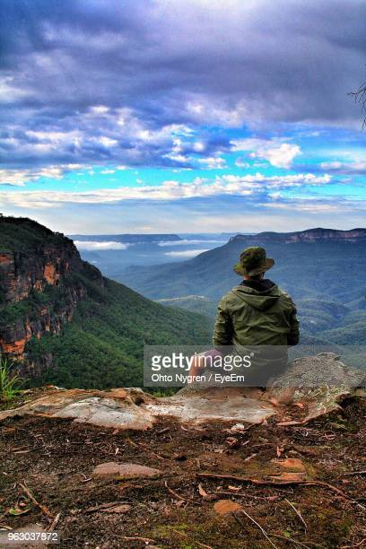rear view of man sitting on rock against mountains - katoomba stock pictures, royalty-free photos & images