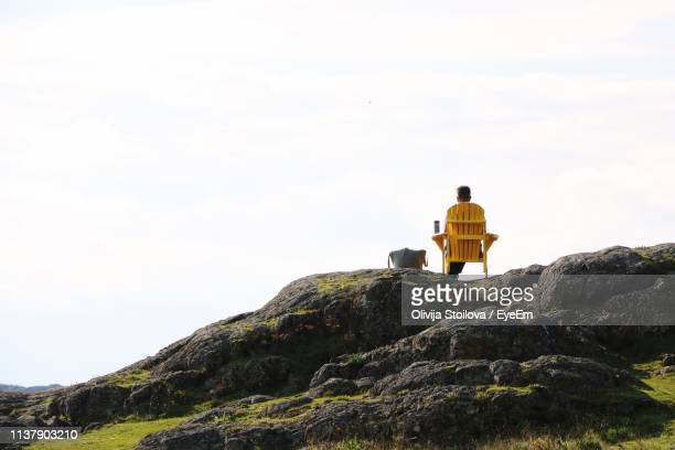 rear view of man sitting on rock against sky - victoria canada stock pictures, royalty-free photos & images