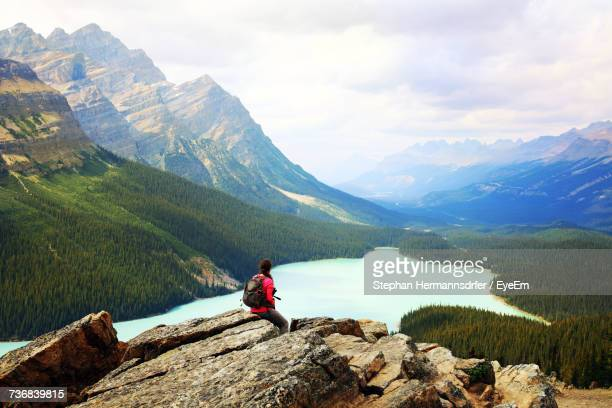 rear view of man sitting on rock by lake against mountains - paisajes de canada fotografías e imágenes de stock