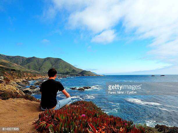 Rear View Of Man Sitting On Rock By Sea Against Sky