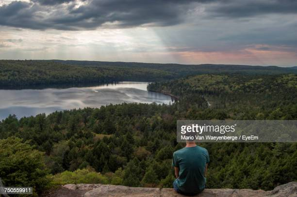 rear view of man sitting on rock over landscape - wilderness stock pictures, royalty-free photos & images