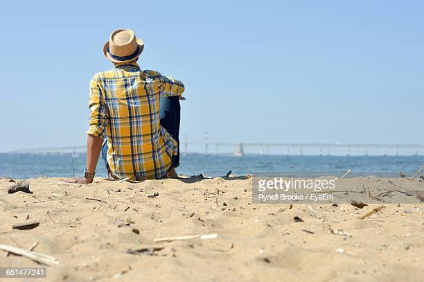 Rear View Of Man Sitting On Sand At Beach Against Sky At Kent Island