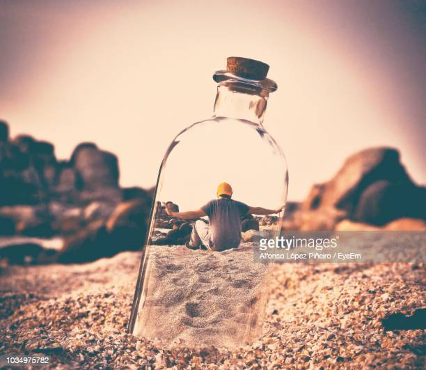 rear view of man sitting on sand seen through glass bottle - optical illusions stock pictures, royalty-free photos & images