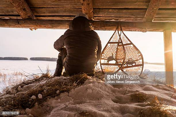 Rear view of man sitting on snowy haystack in barn next to snow shoes, Ural, Russia