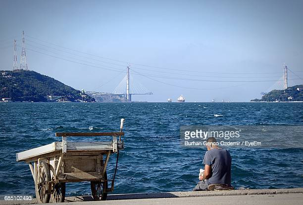 Rear View Of Man Sitting On Steps By Sea