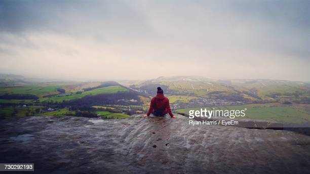 rear view of man sitting on wet cliff against landscape during rainy season - extreme weather stock photos and pictures