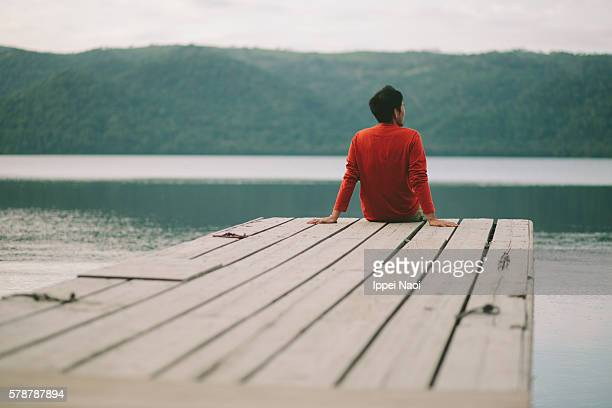 Rear view of man sitting on wooden pier by lake