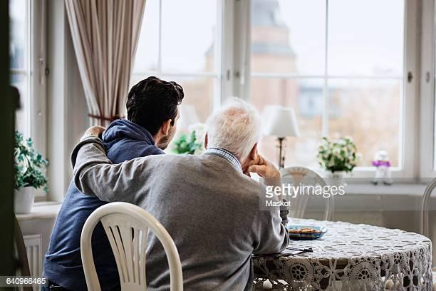 rear view of man sitting with arm around caretaker at nursing home - hand auf der schulter stock-fotos und bilder