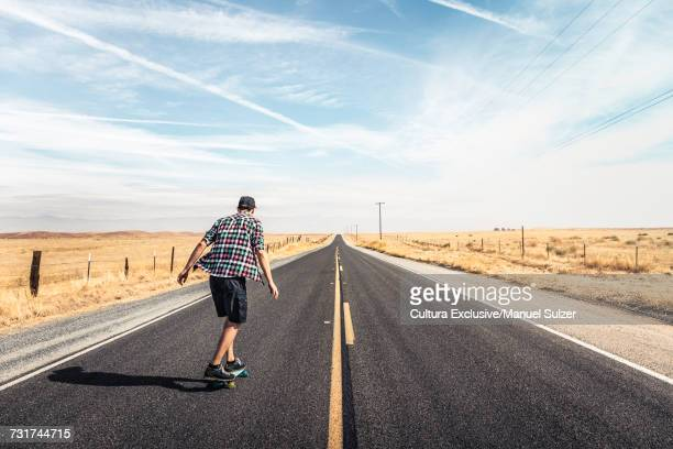 Rear view of man skateboarding on highway through plain landscape, California, USA