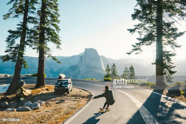 rear view of man skateboarding on road by mountains against clear sky - national park stock pictures, royalty-free photos & images