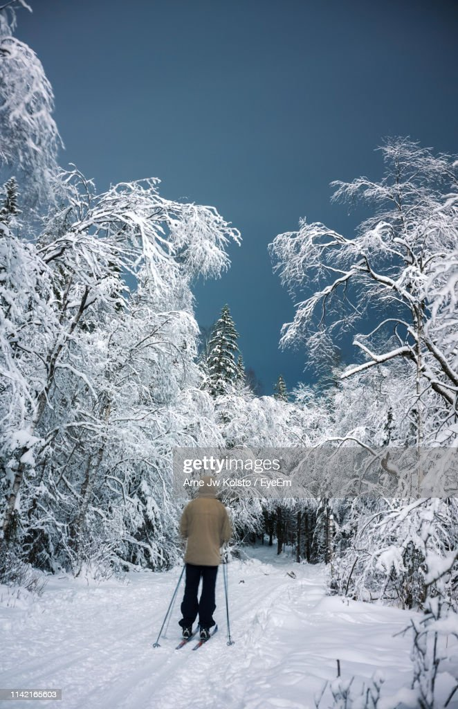 Rear View Of Man Skiing On Snow Covered Field : Stock Photo