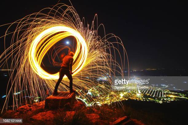 rear view of man spinning wire wool against sky at night - lichtmalerei stock-fotos und bilder