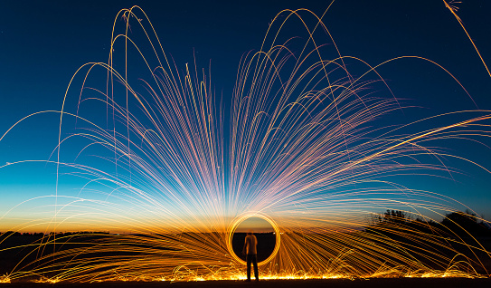 Rear View Of Man Spinning Wire Wool Against Sky During Sunset - gettyimageskorea