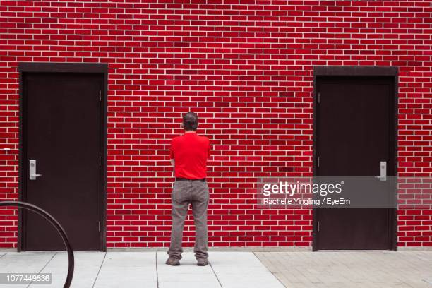 rear view of man standing against brick wall with closed doors - chattanooga stock pictures, royalty-free photos & images
