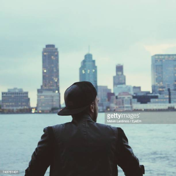 Rear View Of Man Standing Against Cityscape