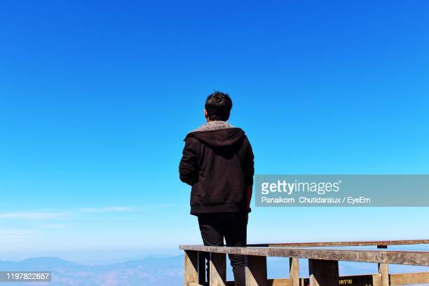 rear view of man standing against clear blue sky - panaikorn chutidaralux stock photos and pictures