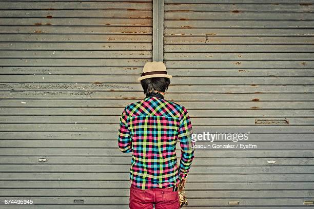 Rear View Of Man Standing Against Closed Shutter Of Store