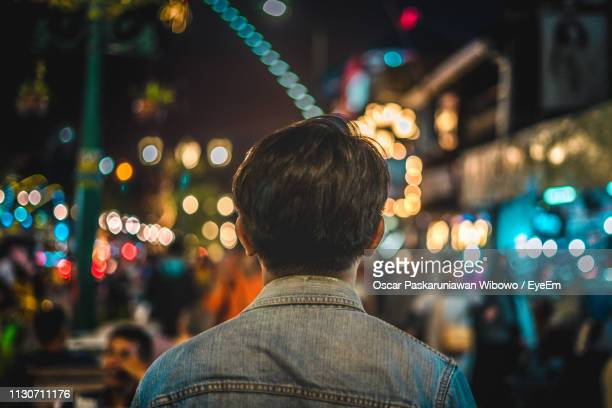 rear view of man standing against illuminated city at night - yogyakarta stock pictures, royalty-free photos & images