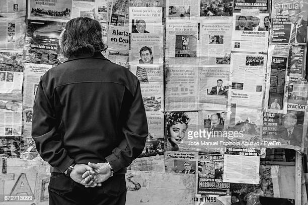 rear view of man standing against newspapers on wall - mexico black and white stock pictures, royalty-free photos & images