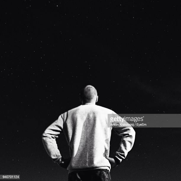 rear view of man standing against star field - arms akimbo stock photos and pictures