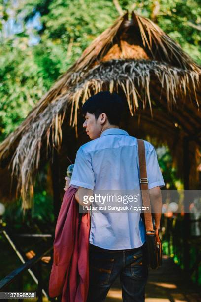 rear view of man standing against thatched roof - pattanasit stock pictures, royalty-free photos & images