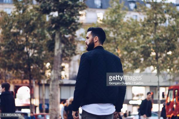 rear view of man standing against trees in city - cadrage aux genoux photos et images de collection