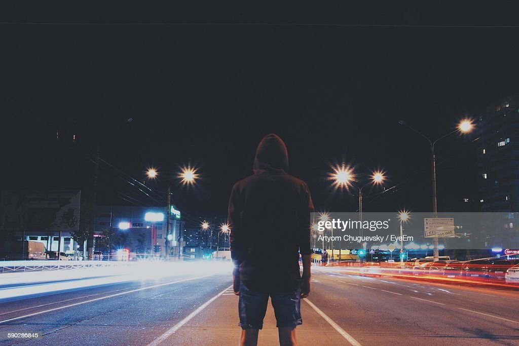 Rear View Of Man Standing Amidst Light Trails On Street At Night : Stock Photo