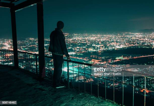 Rear View Of Man Standing At Balcony Against Illuminated Cityscape