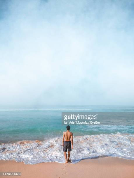 rear view of man standing at beach against sky - denpasar stock pictures, royalty-free photos & images
