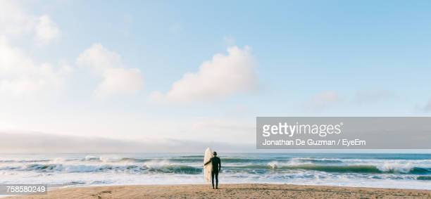 rear view of man standing at beach against sky - california stock-fotos und bilder