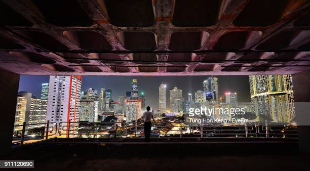 rear view of man standing at building in city during night - south east asia stock pictures, royalty-free photos & images