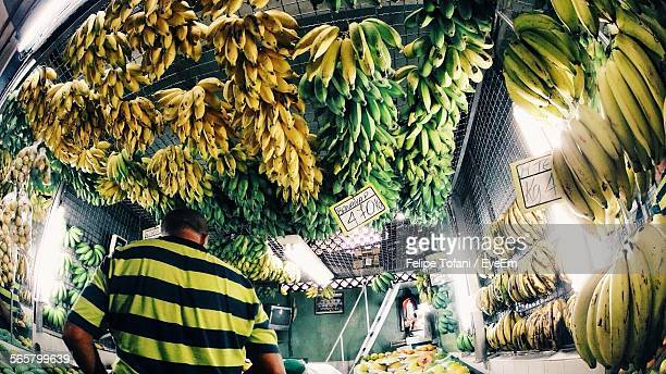 Rear View Of Man Standing At Fruit Stall