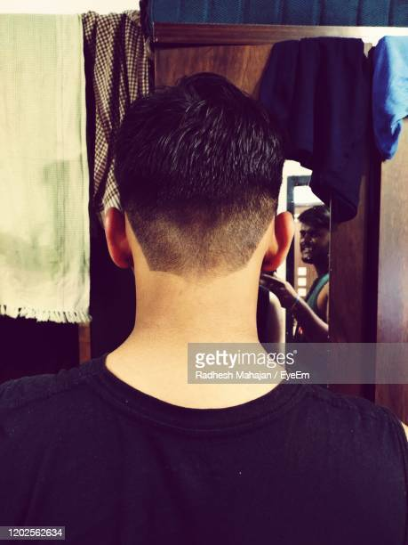rear view of man standing at home - hairstyle stock pictures, royalty-free photos & images