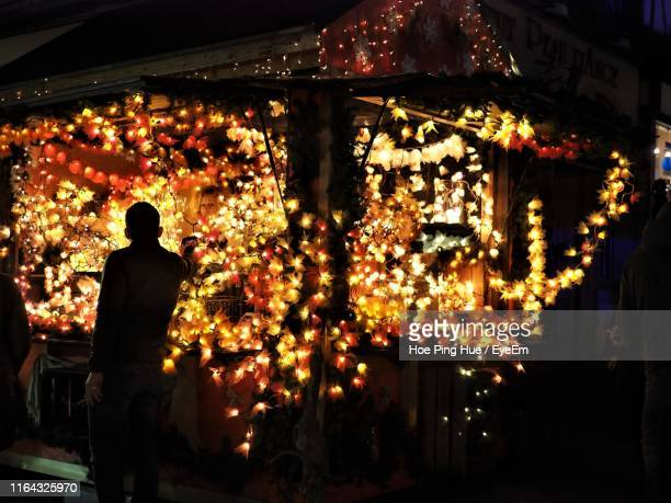 rear view of man standing at illuminated market stall at night during christmas - one night stand stock-fotos und bilder