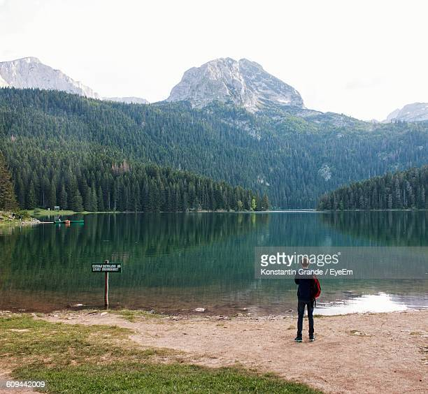 Rear View Of Man Standing At Lakeshore With Rocky Mountains Against Sky