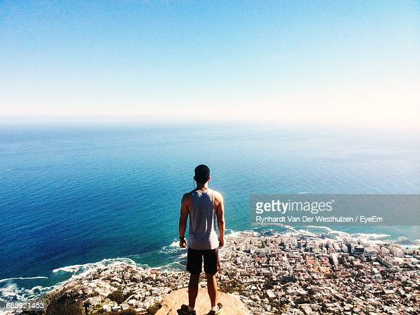 Rear View Of Man Standing At Lion Head Over City While Looking At Horizon