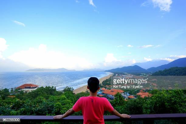 rear view of man standing at observation point against sea - terrasse panoramique photos et images de collection