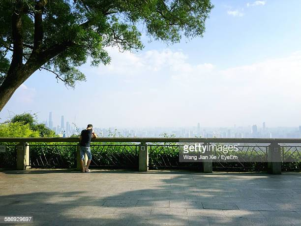 Rear View Of Man Standing At Railing Against Cityscape At Park
